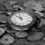 Antique watch and coins in black and white photo